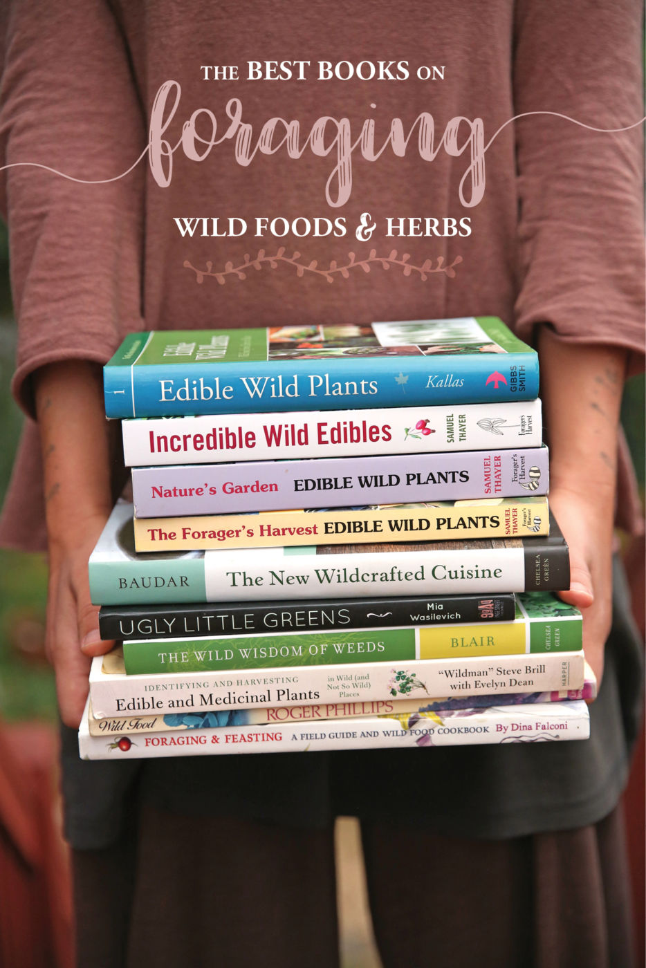 hands holding a stack of books about foraging