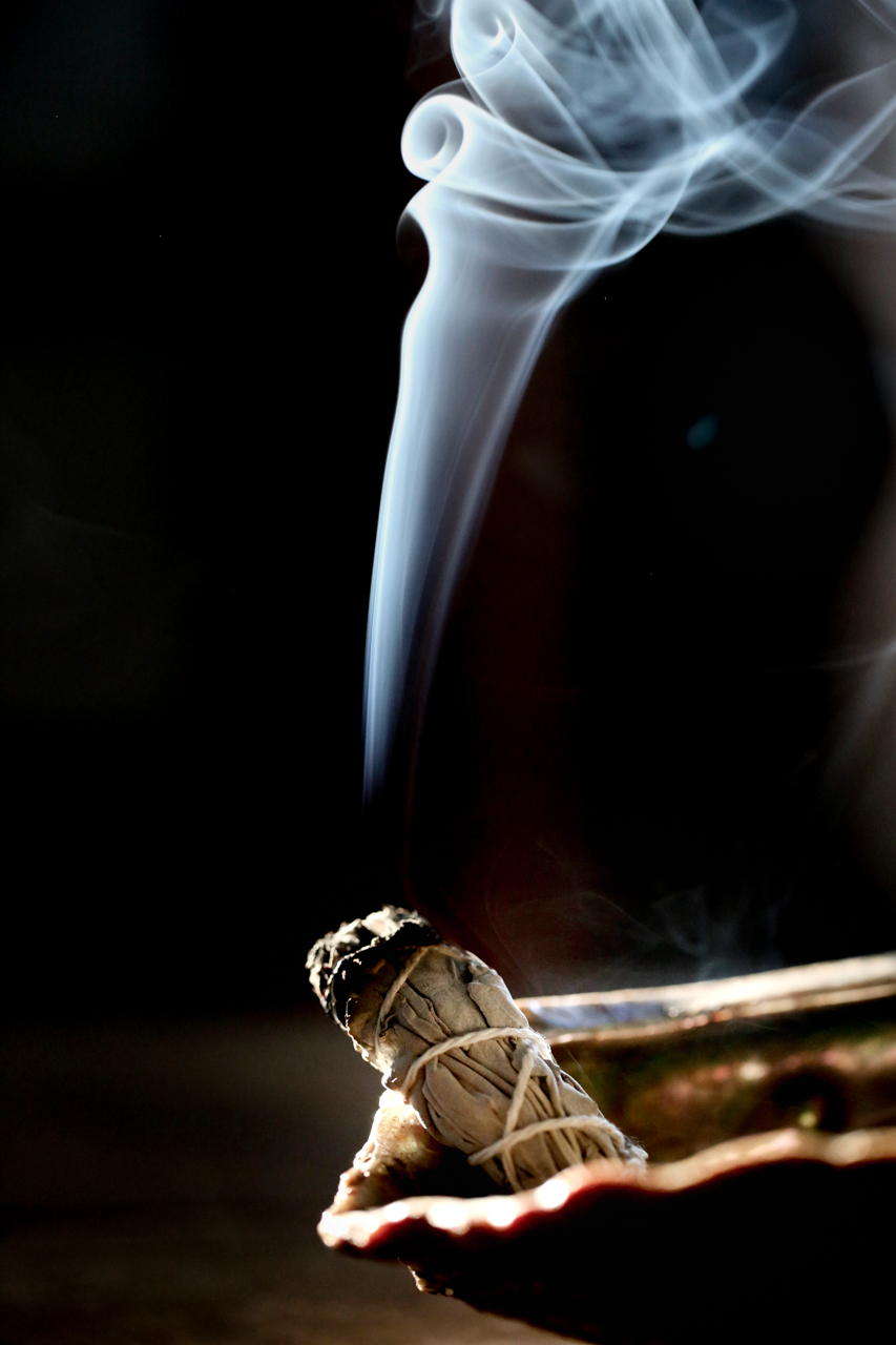 Smoldering aromatic smoke stick resting in an abalone shell