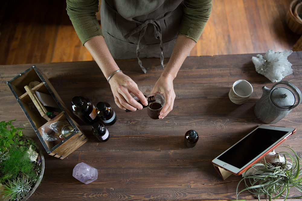 woman mixing tinctures on a table