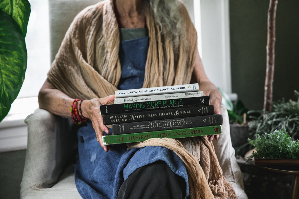 A stack of books sits on a woman's lap